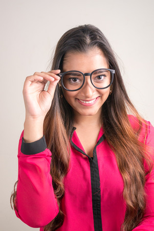 one mid adult woman only: Vertical studio shot of beautiful Indian woman wearing glasses