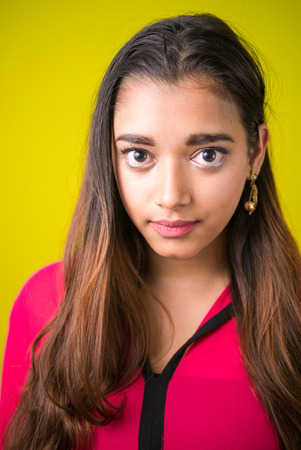 indian subcontinent ethnicity: Vertical studio shot of beautiful Indian woman against yellow background