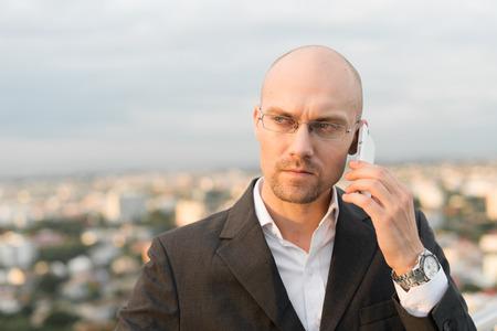 receding hairline: Bald businessman using phone