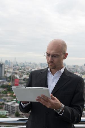 receding hairline: Business man using digital tablet