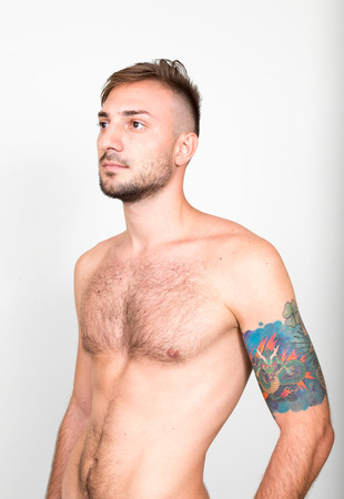 partially nude: Handsome shirtless man with tattoos