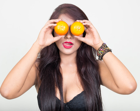 partially nude: Sexy woman with big boobs holding oranges Stock Photo