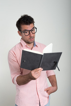 man holding book: Man holding book with funny expression Stock Photo
