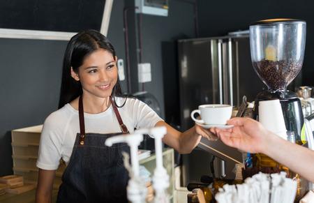 customer focus: Asian woman serving coffee Stock Photo