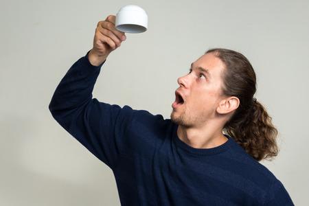 cabeza abajo: Hombre que sostiene la taza de caf� al rev�s