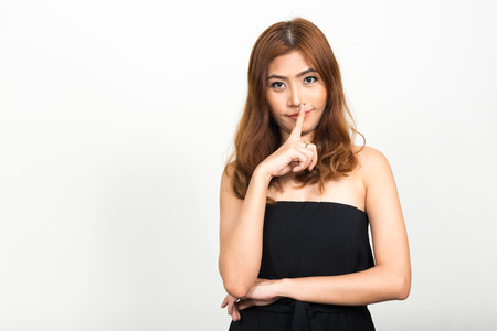 finger on lips: Asian woman with finger on lips Stock Photo