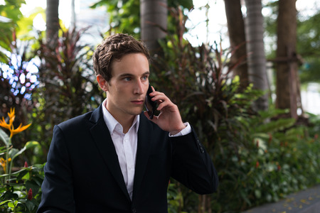 german ethnicity: Portrait of handsome businessman outdoors using mobile phone