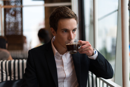 german ethnicity: Businessman sitting and drinking coffee Stock Photo