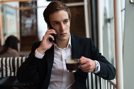 german ethnicity: Businessman using mobile phone and holding coffee cup