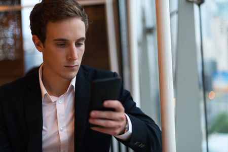 german ethnicity: Businessman sitting and using mobile phone Stock Photo