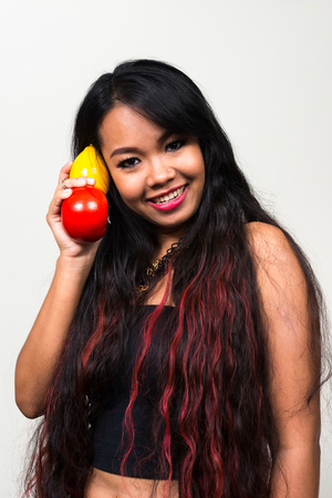 would: Asian woman using fruits like she would talk on phone