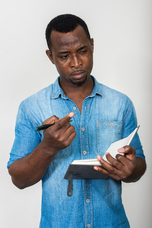 man holding book: Portrait of handsome black African American man holding book and pen Stock Photo