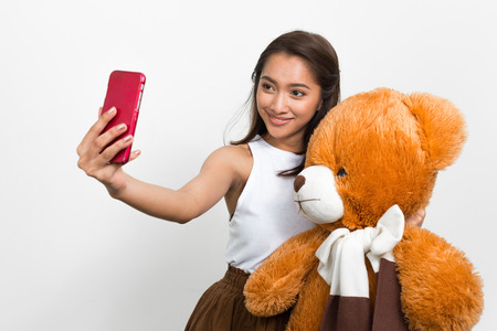 oso de peluche: Mujer que toma la foto selfie con el tel�fono m�vil y la celebraci�n de oso de peluche