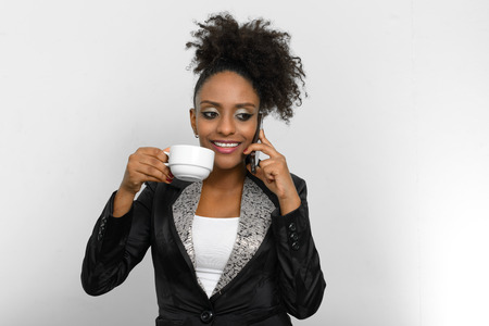 ethiopian ethnicity: African American woman talking on mobile phone and holding coffee cup