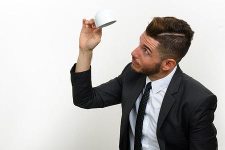 cabeza abajo: El hombre de negocios que sostiene la taza de café al revés