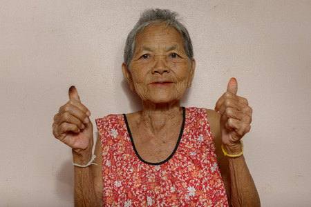 endorsing: Very old Asian woman showing thumbs