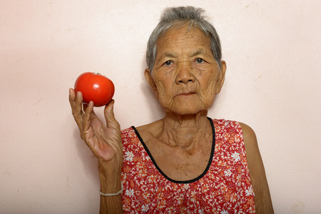 very: Very old Asian woman holding tomato