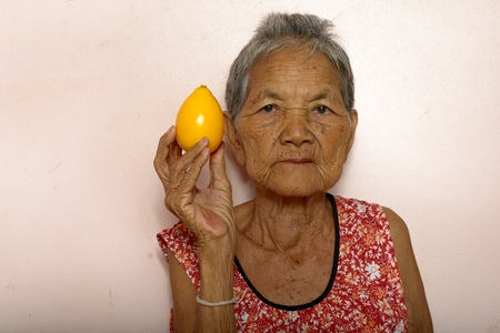 very: Very old Asian woman holding lemon