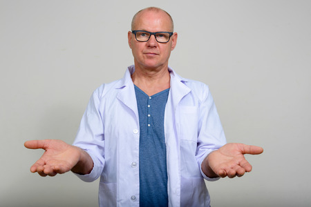 medical decisions: Mature man doctor shrugging shoulders with raised arms