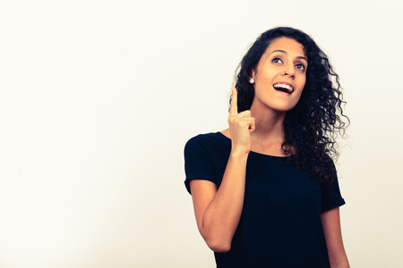 pointing finger up: Portrait of Latin woman with great idea pointing finger up