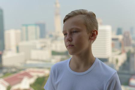 undercut: Portrait of handsome Caucasian boy standing outdoors on rooftop