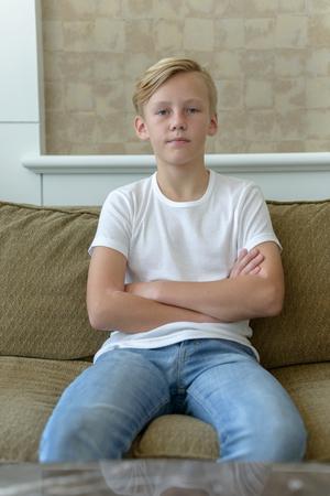 cute boys: Scandinavian young boy sitting on sofa