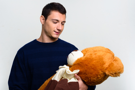 adult toys: Young man holding teddy bear