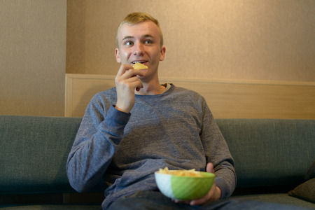 couch potato: Man eating potato chips Stock Photo