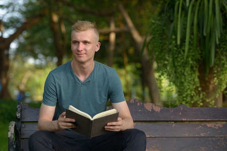 man holding book: Man sitting outdoors in park and holding book