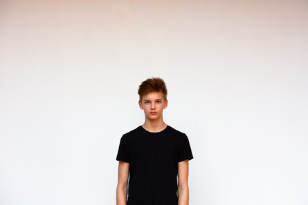 standing against: Teenager boy standing against white background