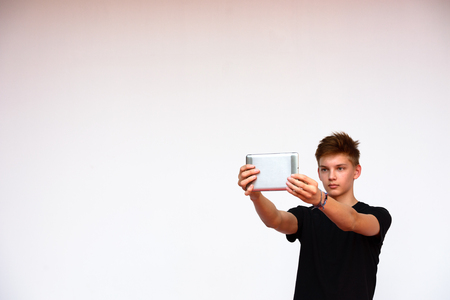 scandinavian people: Teenager boy taking selfie picture with digital tablet