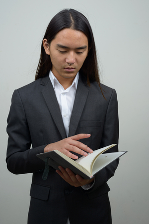 long nose: Asian businessman with long hairstyle reading book