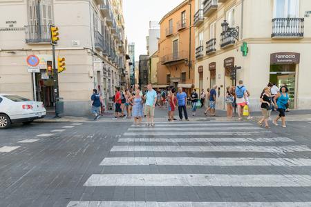 cross street: MALAGA, SPAIN - SEPTEMBER 3: Group of people waiting to cross street