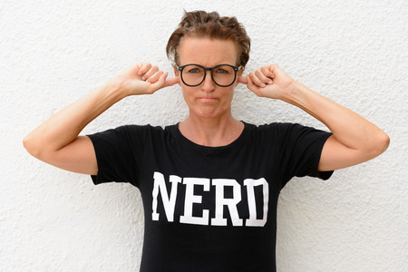 hands covering ears: Mature nerd woman wearing big eyeglasses and standing against white background outdoors while covering her ears with hands