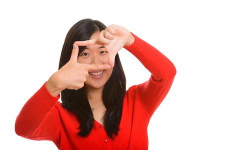 red cardigan: Young happy Asian woman focusing with fingers Stock Photo