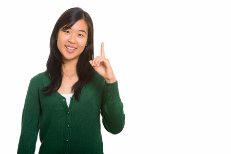 pointing finger up: Young happy Asian woman pointing finger up