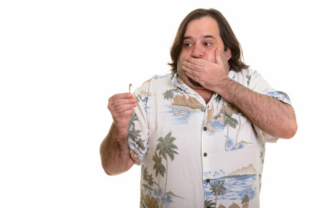 nauseous: Fat Caucasian man eating spicy chili pepper looking nauseous