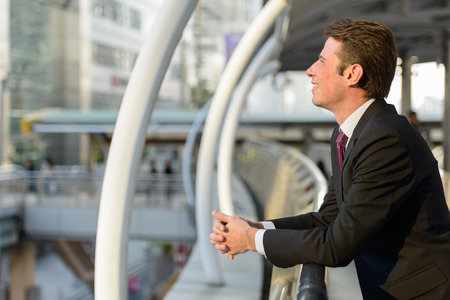 mid distance: Profile view of happy businessman smiling and thinking in footbridge at Bangkok city