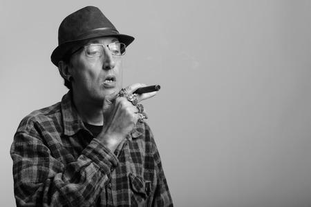 hombre fumando puro: Studio shot of mature gangster man smoking cigar in black and white