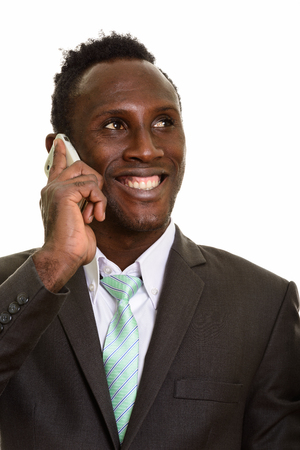 black professional: Face of thoughtful young happy African businessman smiling while talking on mobile phone