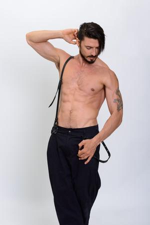 suspenders: Studio shot of handsome man posing with suspenders shirtless