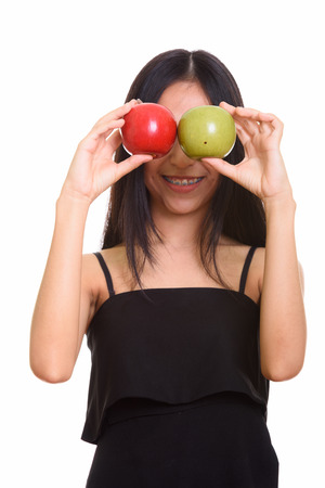 covering eyes: Close up of young happy Asian teenage girl smiling while covering eyes with red and green apple