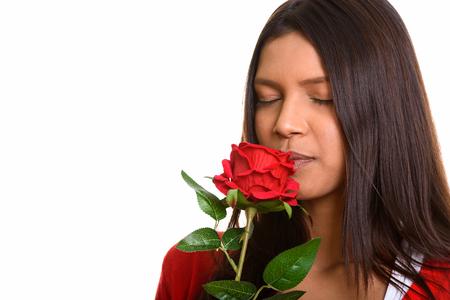 mujer con rosas: Disparo de estudio de la joven y bella mujer con olor a rosa roja brasileña con los ojos cerrados Foto de archivo