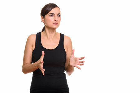 mid distance: Studio shot of beautiful woman looking furious with both hands raised
