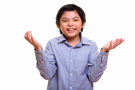 shrugging: Studio shot of happy cute Japanese boy smiling and shrugging
