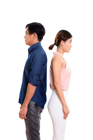 backs: Profile view of young Asian couple with backs against each other