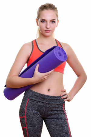 navel piercing: Studio shot of young beautiful teenage girl holding yoga mat and posing ready for gym