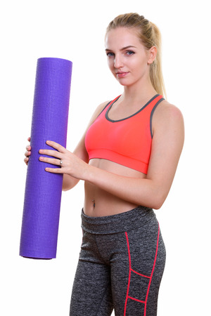 navel piercing: Studio shot of young beautiful teenage girl holding yoga mat ready for gym