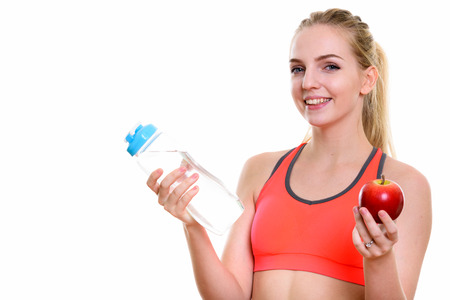 navel piercing: Young happy teenage girl smiling while holding water bottle and red apple ready for gym