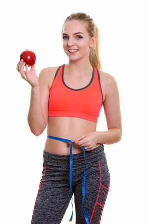 navel piercing: Young happy teenage girl smiling while holding red apple and measuring waist ready for gym